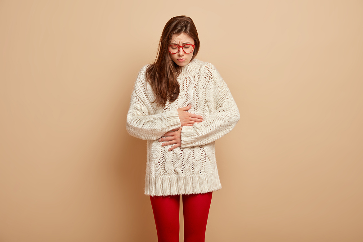 Dissatisfied woman suffers from bellyache, keeps hands on stomach, feels cramps, being very hungry, has sad expression, dressed in oversized white jumper and red tights. People, diarrhea, dieting